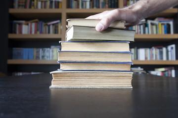 Mano sobre libros con librería al fondo