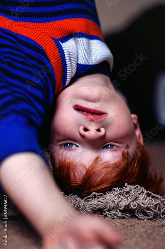 Redhead boy hanging upside down off a bed