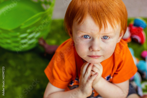 Redhead boy playing outside with his toys