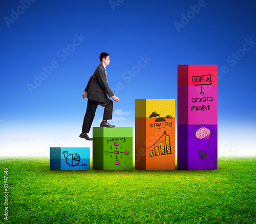 Attractive businessman walking on graph of success
