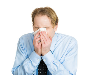 Sick man having cold, allergies, sneezing