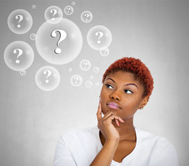 Woman thinking, grey wall background with bubbles questions