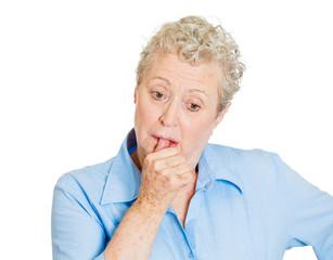 Headshot older woman sucking thumb, thinking on white