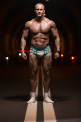 Bodybuilder Performing Front Relaxed Poses In Tunnel