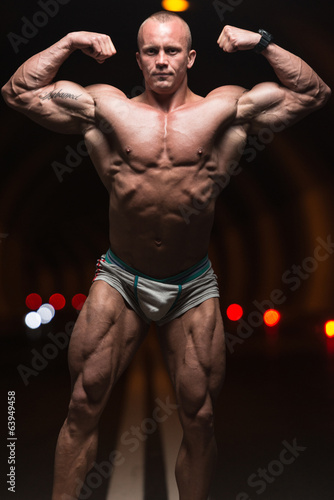 Bodybuilder Performing Front Double Biceps Poses In Tunnel
