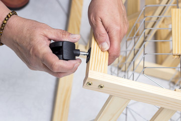 A carpenter builds a small white table with a screwdriver