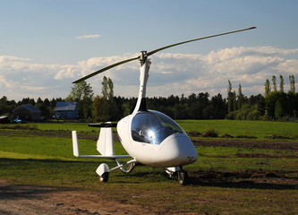 White gyroplane parked on the private airfield