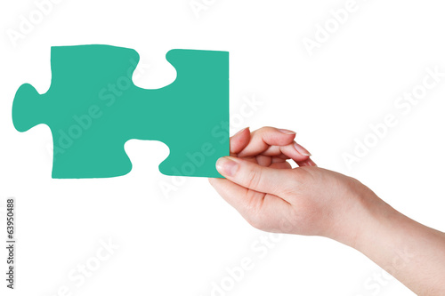 female hand with green puzzle piece