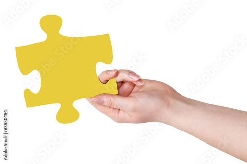 female hand with yellow puzzle piece