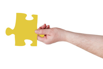 male hand with yellow puzzle piece