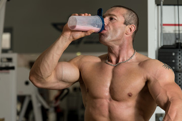 Muscular Man Drinking Water From Shaker