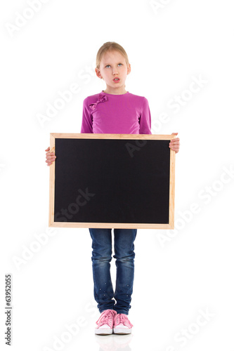 Grimacing schoolgirl standing with blackboard.
