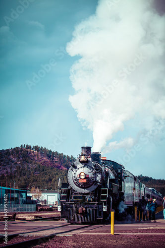 Old steam locomotive against blue cloudy sky, vintage train