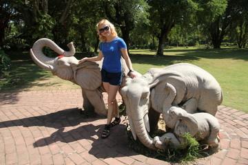 девушка на фоне статуй слонов