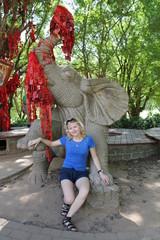 девушка сидит рядом со статуей слона