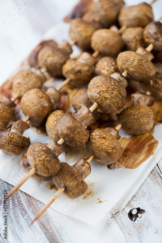 Baked champignons skewers, vertical shot, close-up