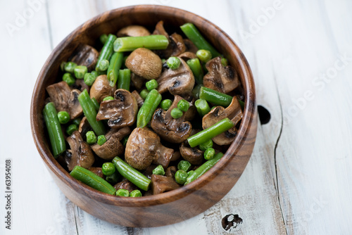 Roasted champignons with vegetables in a wooden bowl