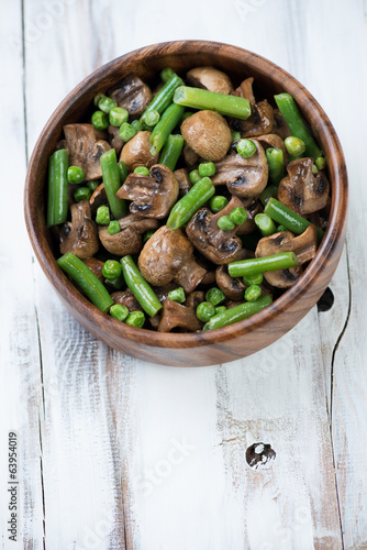 Wooden bowl with roasted champignons, peas and beans, above view