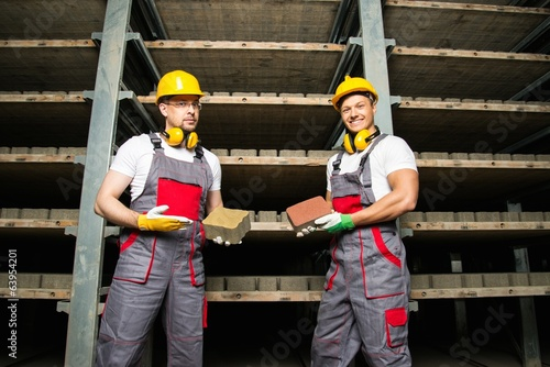 Two workers in a storage room on a factory holding their product