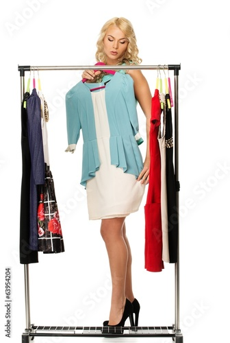 Blond woman choosing clothes on a rack