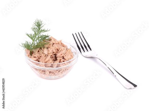 Canned tuna in glass bowl with dill and fork.