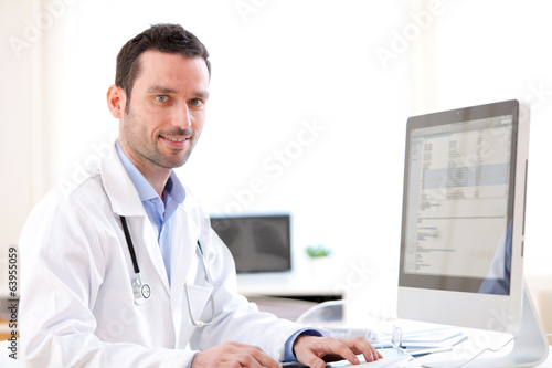 canvas print picture Portrait of a young doctor analysing a radiography