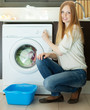 woman loading clothes into the washing machine  in home