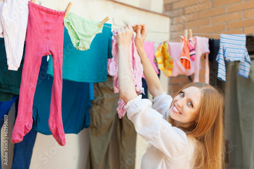 Positive girl drying clothes