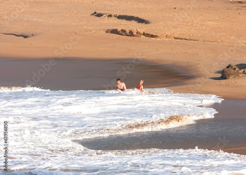 happy couple bathes in surf