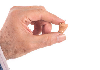 CIC hearing aid between fingers
