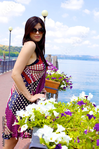 Beautiful italian woman posing in front of colored flowers