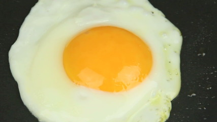 Slow zoom on an egg frying in a fry pan.