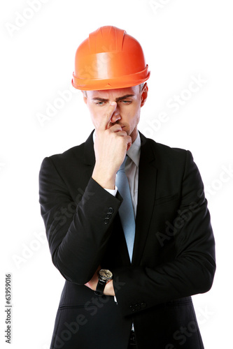 Portrait of a pensive businessman in orange helmet