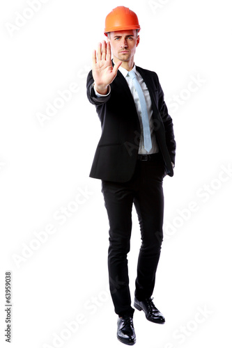 businessman in helmet showing stop gesture