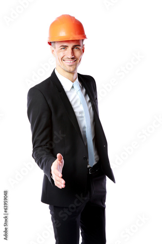 businessman in helmet offering handshake over white background