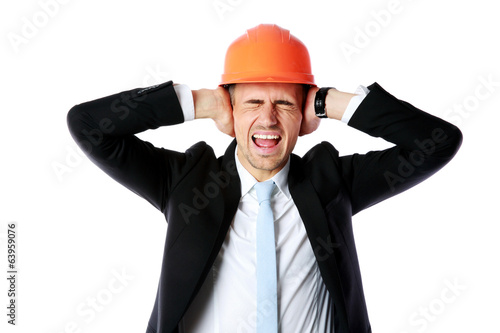 Businessman in helmet covering his ears over white background