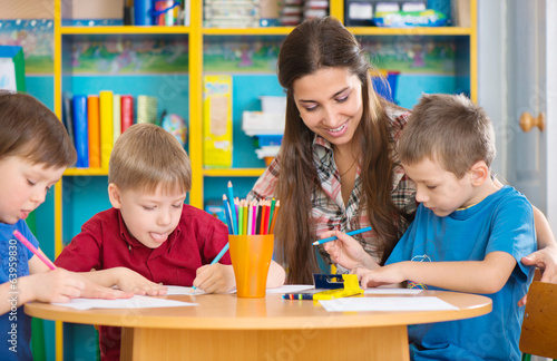 Cute children drawing with teacher at preschool class