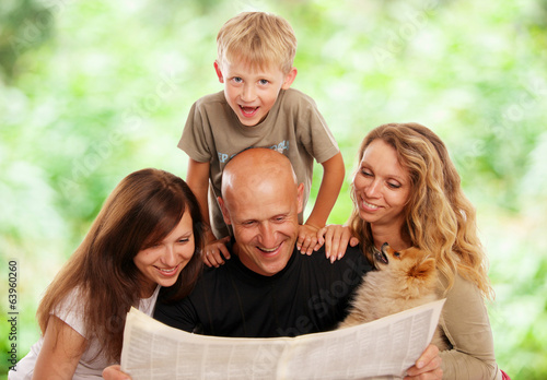Family reads the newspaper outdoors - 63960260