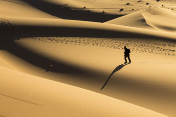 Man walking on dunes in desert
