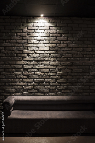brown sofa illuminated from above with brick background