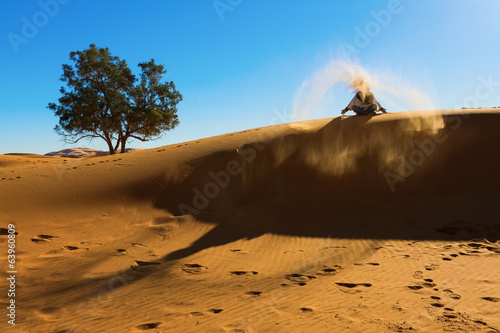Berber playing and throwing with sands in Desert Sahara, creatin