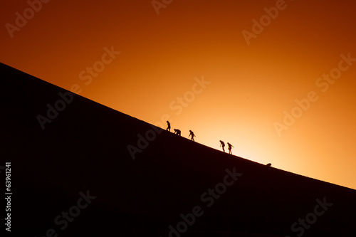 Silhouettes of a team trying to clime a hill. Sport and active l