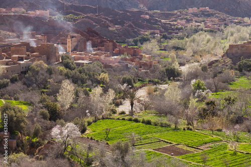 Old city in Morocco with mosque in background and green landscap
