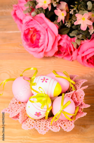 Easter decorative eggs and bouquet of pink flowers