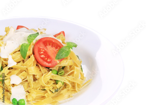 Pasta tagliatelle with pesto sauce and basil.