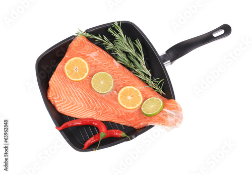 Raw salmon on frying pan with rosemary.