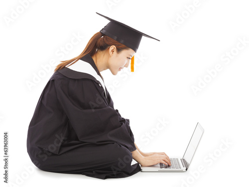 female graduation sitting and  typing on a laptop