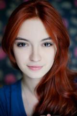 Портрет рыжеволосой девушки на фоне цветной стены