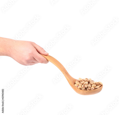 Hand holding spoon with pistachios.