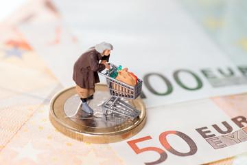 Alte Frau mit Einkaufswagen auf einem Geldstück mit Banknoten